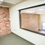 1250 Fulton. Interior photo of mezzanine office space. Inside large office space with window overlooking the ground floor retail space. Red brick wall and gray carpet.