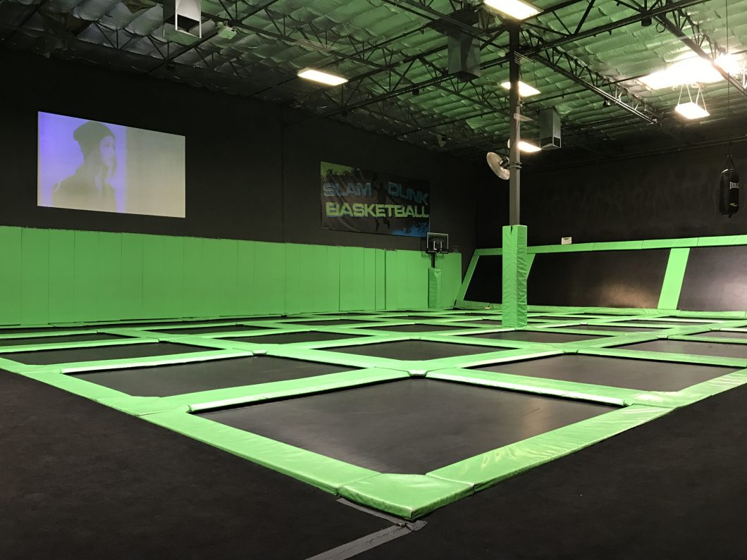 Interior photo of a trampoline arena business. Several trampolines connected together. Interior painted black and lime green.