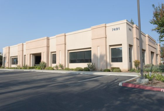 7941 N. Remington Ave., Fresno. Large commercial building with parking lot. Building painted shade of beige and peach