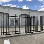 1310 N. Crystal Ave., Fresno. Industrial property for lease. Exterior photo of security-gated parking lot. Black wrought iron rolling gate in foreground. Concrete block warehouse in background. Photo shows three roll-up doors. Warehouse painted gray with blue doors.