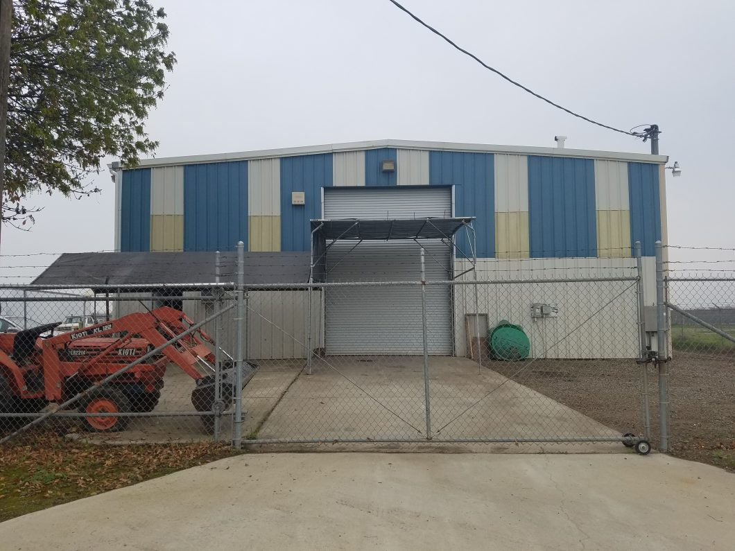17952 Baldwin St., Madera. Exterior photo of metal freestanding building with large roll-up door. Fenced rolling gate in the foreground.