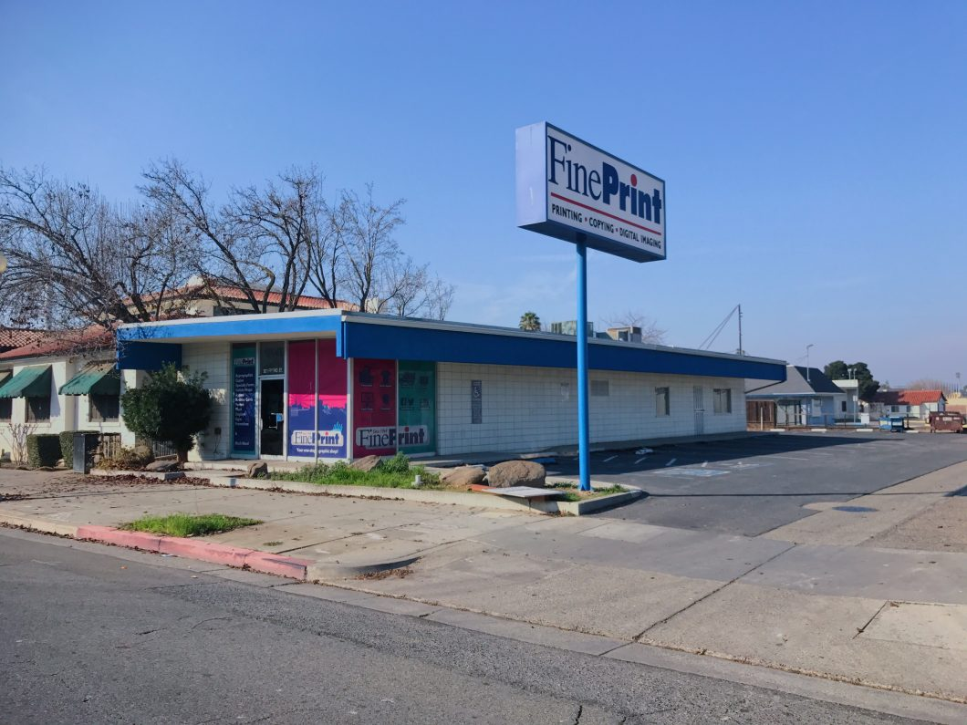 2621 Fresno St., Fresno. Exterior photo taken at an angle showing front and side of the building, as well as freestanding pole signage and parking lot. Photo taken from Fresno Street. Building painted blue and white.