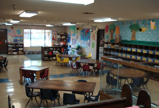 Interior photo of daycare center for sale. Several small tables and chairs for children. Vibrant decor.