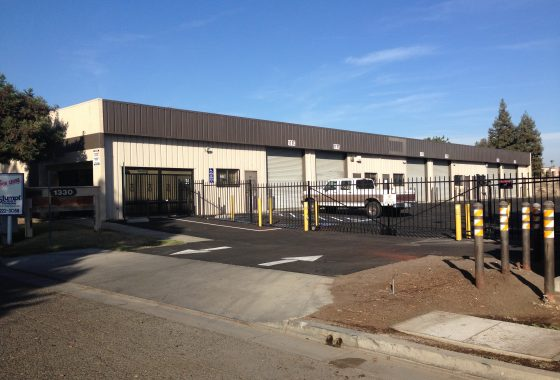 Exterior photo of industrial property. 1330 N. Hulbert Ave., Fresno. Photo taken from Hulbert Ave. Rolling security gate and metal warehouse painted beige and brown.