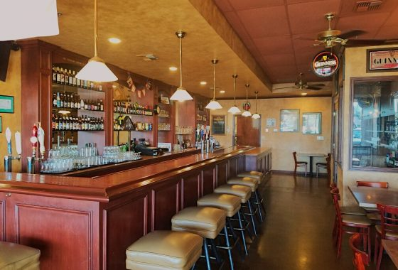 Beer and wine business for sale. Interior photo of bar countertop and stools. Warm red and brown tones. Warm-colored lighting. Bottles of beer and glasses in the background.