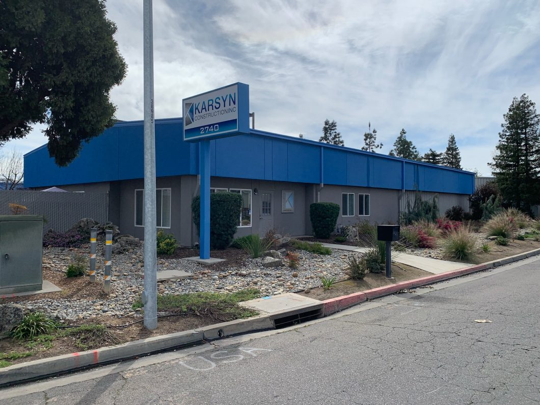 2740 N. Sunnyside Ave., Fresno. Office/warehouse for lease. Photo of exterior. Building painted gray and blue. Freestanding pole signage that reads Karsyn Construction. Drought tolerant landscaping.