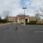 Preschool for sale. Exterior photo of parking lot and front side of the building. Beige stucco building.