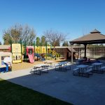 Preschool for sale. Exterior photo of playground equipment, tables, and shaded area.