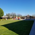 Preschool for sale. Exterior photo of play area. Large grass area and playground equipment.