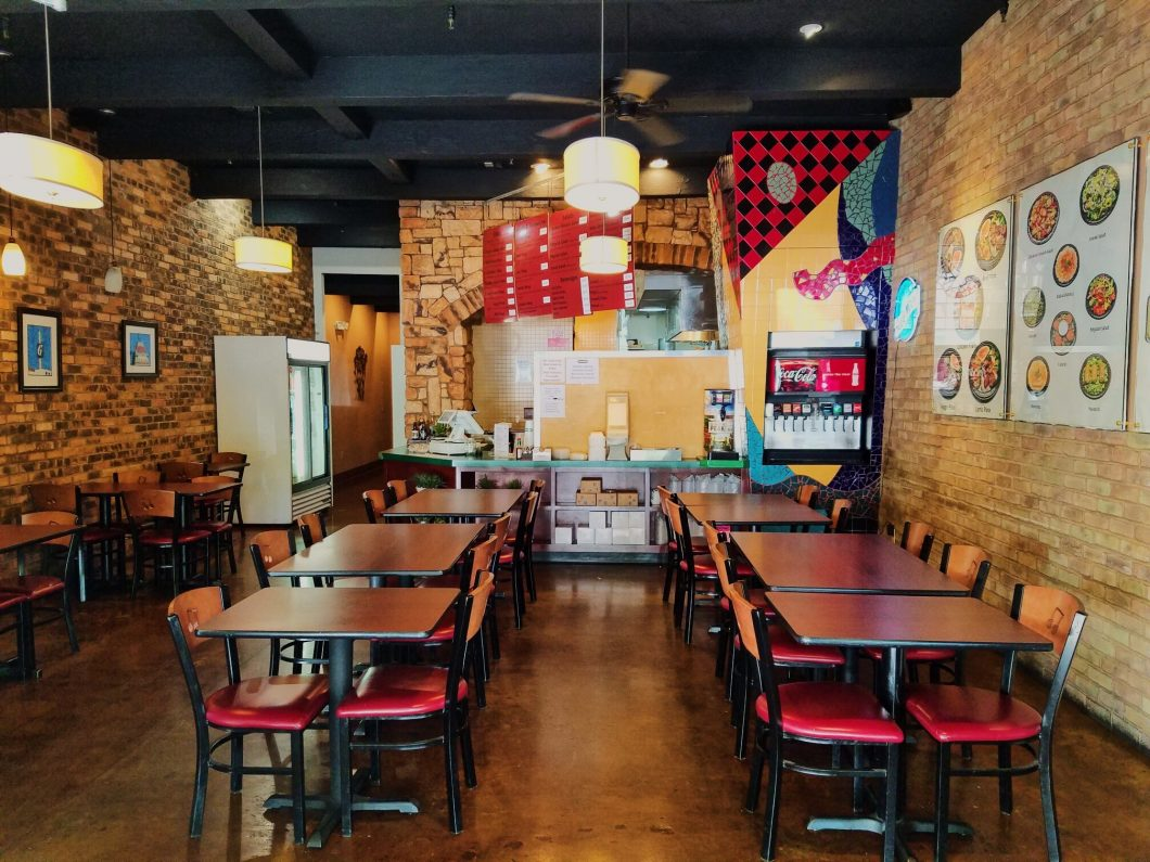Casual dining restaurant for sale. Interior photos of table and seating, front counter, and menu. Prominent interior colors are red, yellow, and light brown.