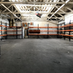 1776 H St., Downtown Fresno - Interior photo of open warehouse space with metal shelving along walls.