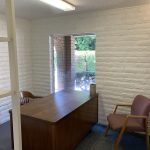 3210 N. Fruit Ave., Fresno. Interior photo. Small private office. White painted brick. Desk and two chairs.