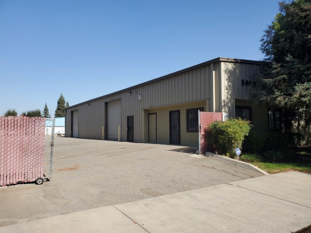 metal warehouse with fenced yard. Gray exterior. Two roll-up doors. Located at 5809 E. Brown Ave., Fresno