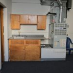 Interior photo. Kitchenette. Brown cabinets. Gray countertop. Heating/cooling unit next to kitchenette.