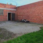 Exterior photo of backyard patio. Red brick walls. Concrete pad. A little grass.