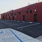 Exterior photos of the back potrion of the building and the parking lot. The building is painted red.