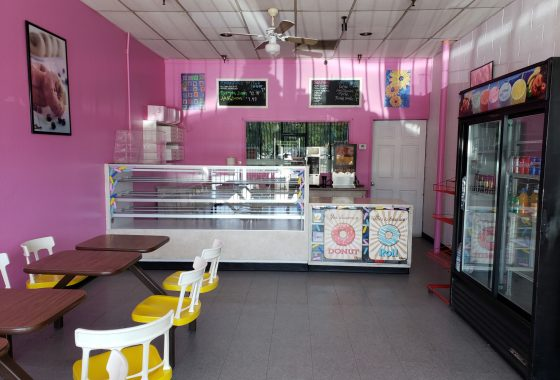 Interior of donut shop. Pink walls. Yellow seats. Donut display case. Soda/drinks case.