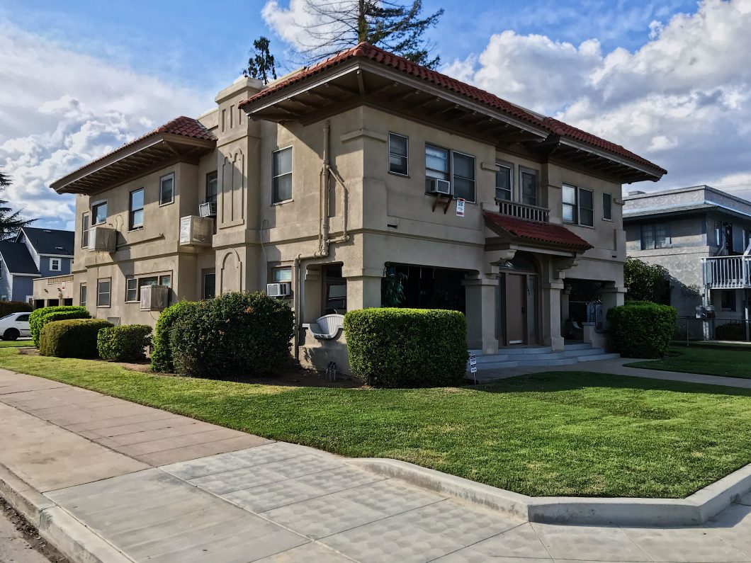 Two-story 6-unit apartment complex. Brown stucco exterior with tile roof.