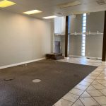 Interior picture of open room. Beige walls. Brown carpet and beige tile.