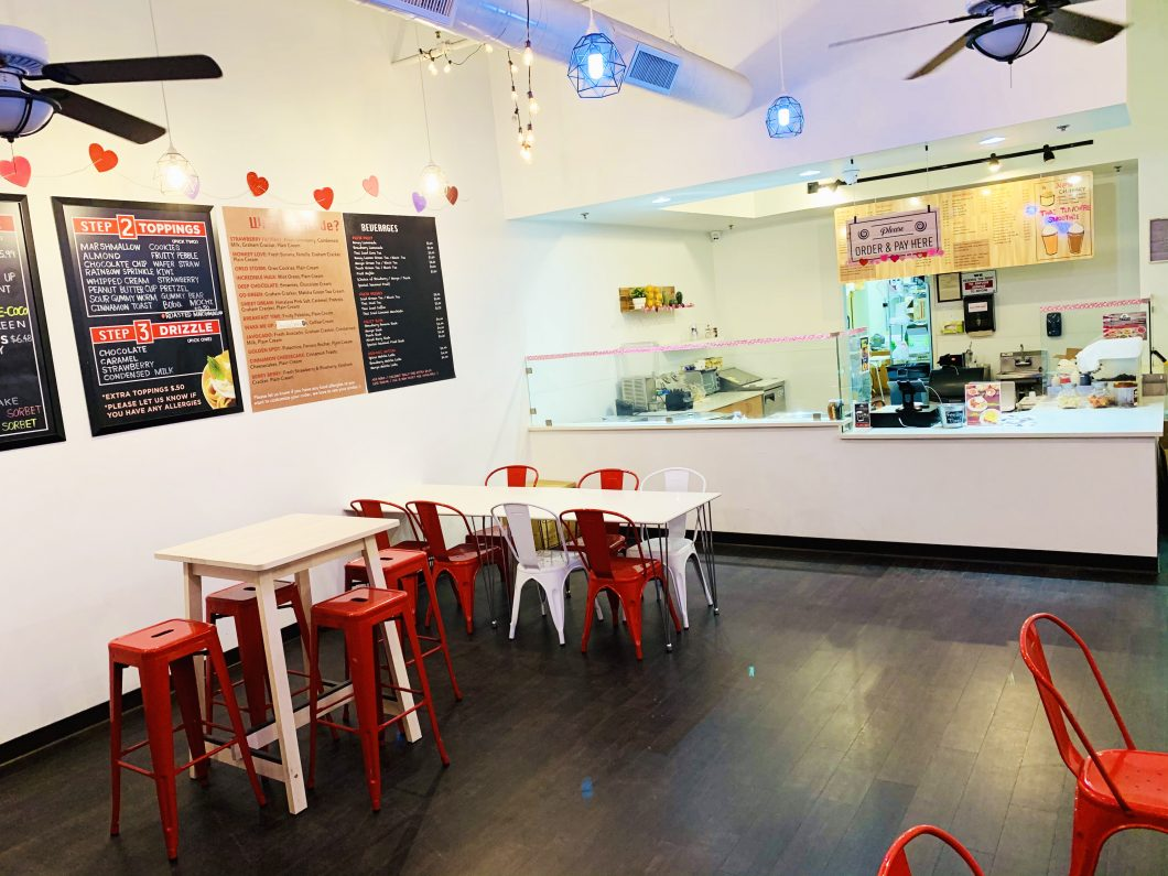 Interior photo of a rolled ice cream shop listed for sale. View point from the front entrance. Black hard flooring, red metal stools, and white high tables. Ordering counter top in the background.