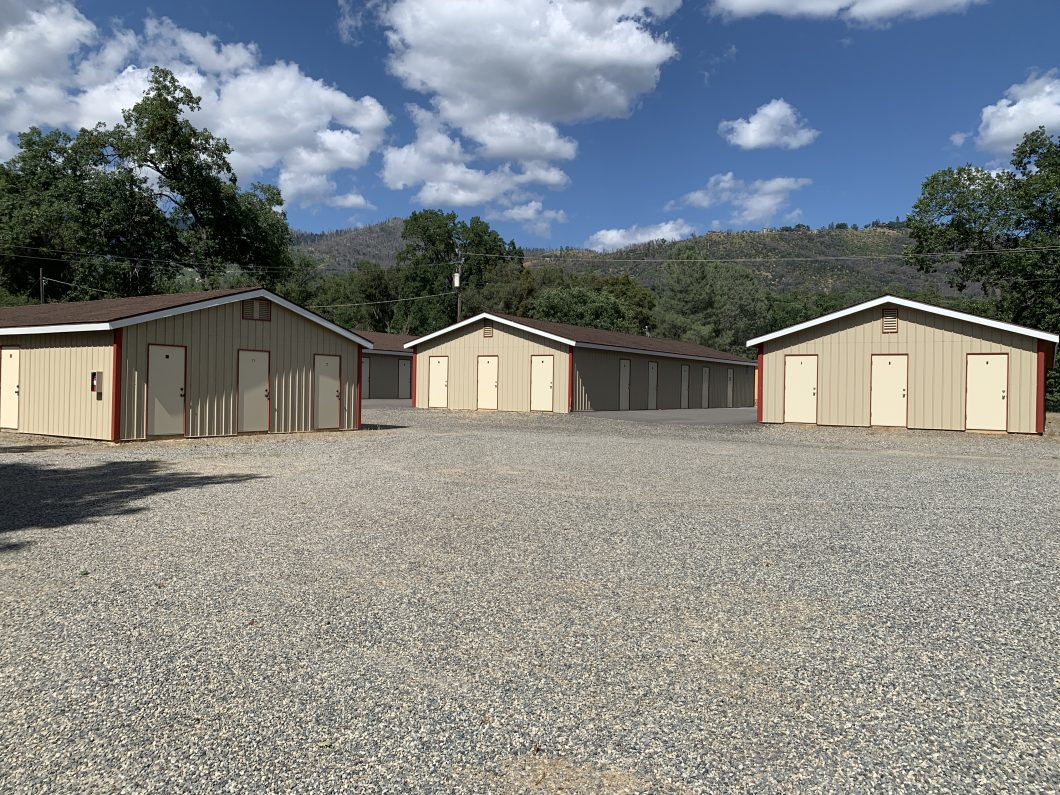 Exterior photo of North Fork mini storage. Several small units clustered together. Light brown buildings and beige doors. Gravel road and lot.