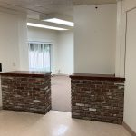 Interior photo of office building at 121 N. Lake St., Madera. Photo shows the front entrance. Front counter is wrapped with dark brown-red brick. Light brown tile flooring in front. Brown carpet in back. White walls.