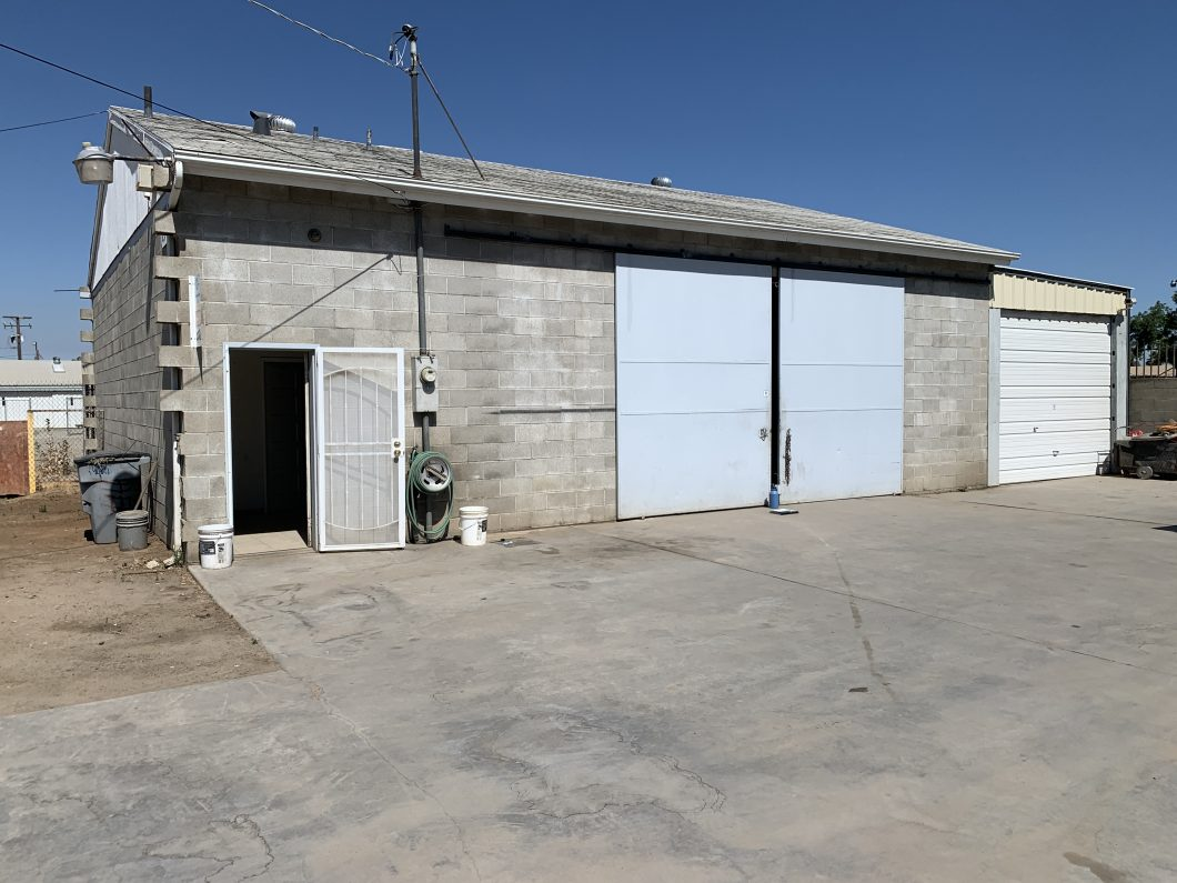 Exterior photo of auto repair industrial building at 2336 W. Belmont Ave., Fresno. View looking at the front of the building. Gray block building. Light blue large barn doors. Front door with white security gate.