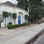1145 E. Shaw Ave., Fresno - Exterior photo of a small freestanding office building. White stucco with blue door and blue accents.