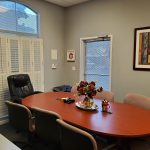 Interior photo of 1145 E. Shaw Ave., Fresno. Conference Room. Gray walls with white trim. Large windows. Conference table.